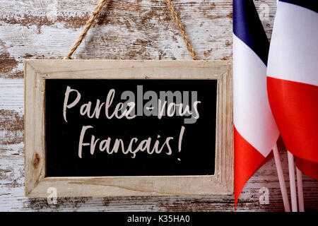 a wooden-framed chalkboard with the question parlez-vous francais? do you speak French? written in French, and some - Stock Photo