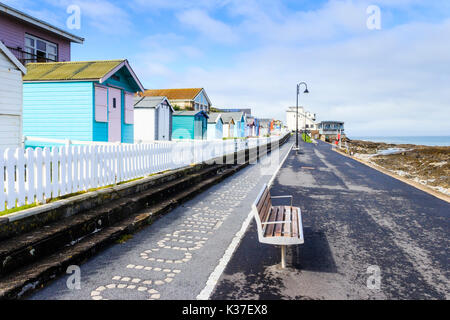 Turquoise blue painted beach huts and white picket fence on the promenade at Westward Ho!, Devon, England, UK - Stock Photo