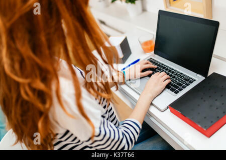 Red haired woman working on laptop - Stock Photo