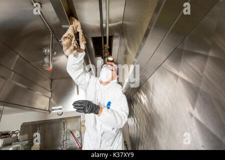 Commercial kitchen worker washing up at sink in professional kitchen - Stock Photo