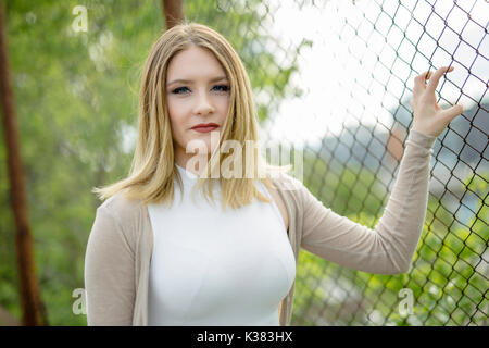 Closeup of pretty young woman standing near chain link fence - Stock Photo