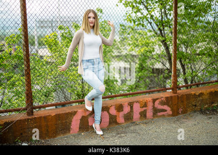 pretty young woman standing near chain link fence - Stock Photo