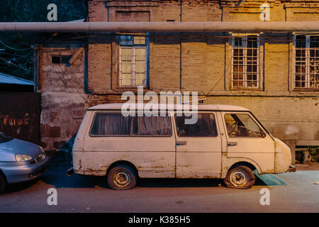 Old car with flat tire on the road. - Stock Photo