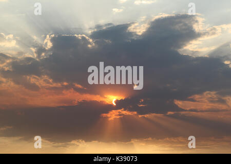 Evening sun behind clouds with sun rays. - Stock Photo