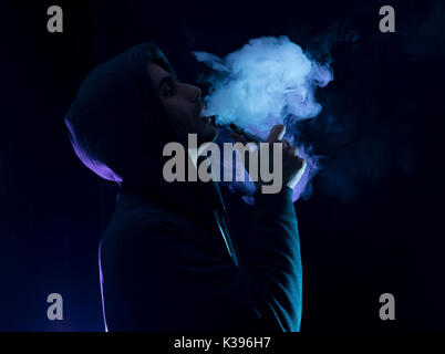 Isolated young man smoking an electronic cigarette on a dark background, holding a vaping device. - Stock Photo