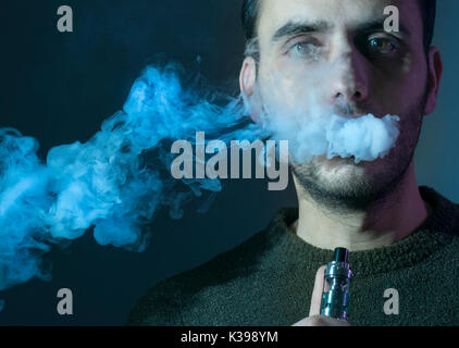 Isolated young man on a dark background holding an electronic cigarette, vaping device, mod, e-cig. - Stock Photo