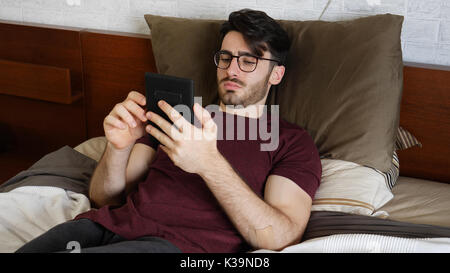 Young man on bed reading with ebook reader - Stock Photo