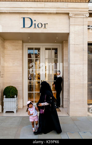 A Muslim Woman Wearing A Burka Walks Past The Dior Fashion Store In New Bond Street, London, UK - Stock Photo