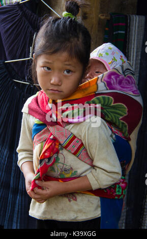 Vietnamese child carries little brother on her back, while looking plaintive, but never begging on Oct 21, 2011 - Stock Photo