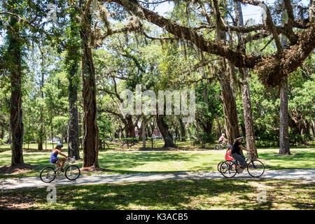 Jekyll Island Georgia barrier island historic district bike path bicycle cycling girl family - Stock Photo