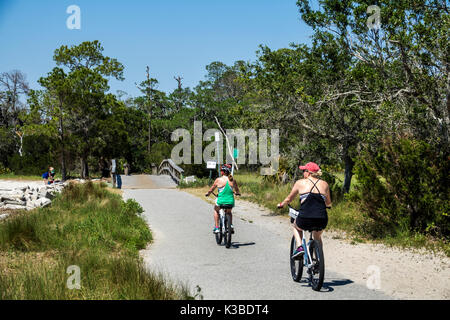 Jekyll Island Georgia barrier island pathway Clam Creek Picnic Area bike trail pathway woman friends biking riding - Stock Photo