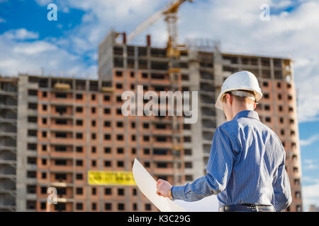 Architect in helmet with blueprints looks at camera in a building site - Stock Photo