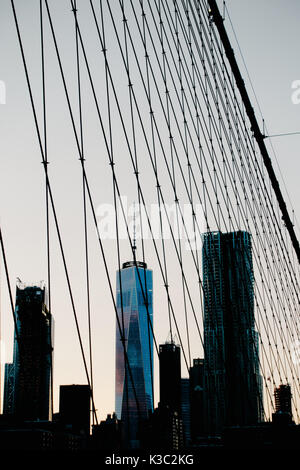 Manhattan skyline at dusk featuring the One World Trade Center taken not only from, but through the cables of Brooklyn - Stock Photo
