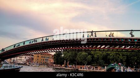 People walking over the Ponte della Costituzione (Constitution Bridge) in Venice, Italy at sunset - Stock Photo