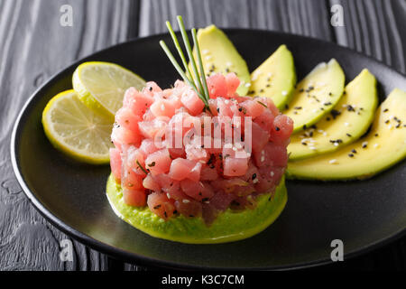 Tartar from fresh raw tuna with spices close-up on a plate. horizontal - Stock Photo