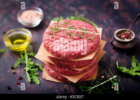 Fresh raw homemade minced beef steak burger with spices on black background - Stock Photo