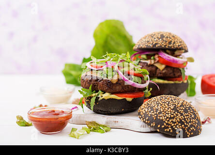 Black big sandwich -  black hamburger with juicy beef burger, cheese, tomato,  and red onion on light background. - Stock Photo