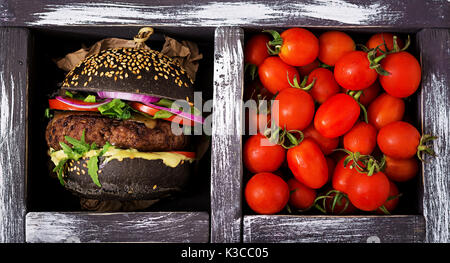 Black big sandwich -  black hamburger with juicy beef burger, cheese, tomato,  and red onion in box on black background. - Stock Photo