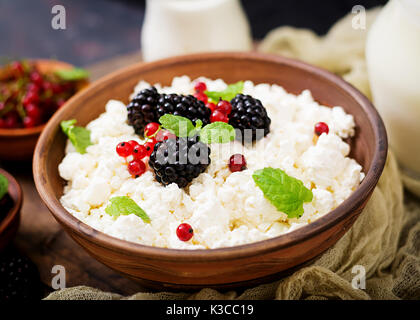 Cottage cheese with blackberries in a  bowl. - Stock Photo