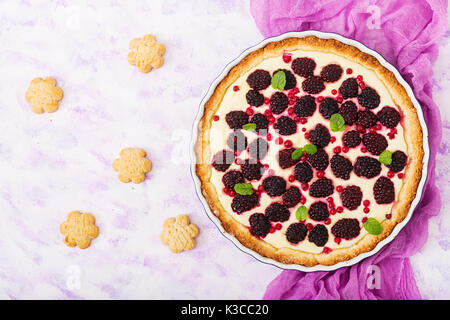 Tart with blackberry and cheesecake cream decorated with mint leaves. Top view. Flat lay - Stock Photo