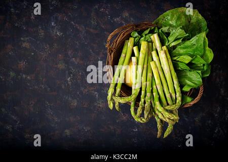 Fresh asparagus in basket on dark  background. - Stock Photo
