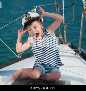 funny little boy wearing captain hat sitting aboard luxury boat with water behind in summer - Stock Photo