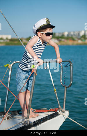 Experienced funny little boy captain wearing captain hat and fashionable sunglasses on board of luxury boat in summer - Stock Photo