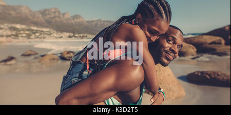 African man piggybacking woman at the beach. Romantic young couple on beach vacation. - Stock Photo