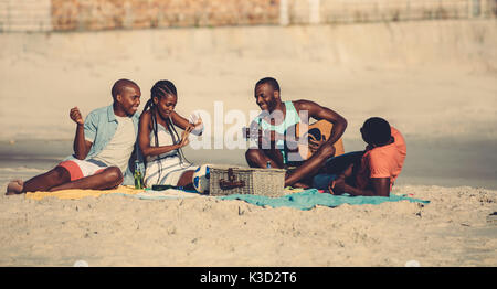 Group of young people hanging out at the beach. Young afro american man playing guitar for friends. - Stock Photo