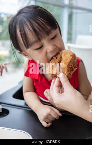 Asian Chinese mother and daughter eating fried chicken at indoor restaurant - Stock Photo