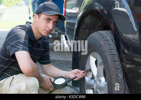 a young man controls car tire pressure - Stock Photo