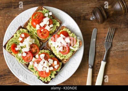Toasts with mashed avocado, tomatoes and crumbled feta cheese on white plate on wooden table. Top view. Healthy - Stock Photo