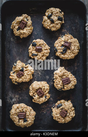 Freshly baked oatmeal raisin cookies with dark chocolate, cinnamon and nuts on old rusty cookie sheet. Table top - Stock Photo