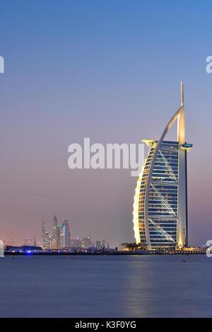 Dubai, United Arab Emirates - Oct 10, 2016: The illuminated Burj Al Arab note and marinal at dusk, view from Jumeira - Stock Photo