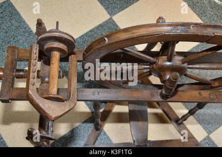 An old wooden spinning wheel - Stock Photo