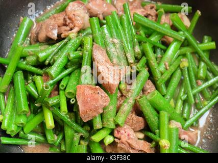 Chinese Cuisine and Food, Stir Fried Flowering Chinese Garlic Chives or Ku Chai with Chicken Livers. - Stock Photo