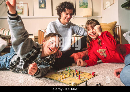 Mother with two children while playing Ludo - Stock Photo
