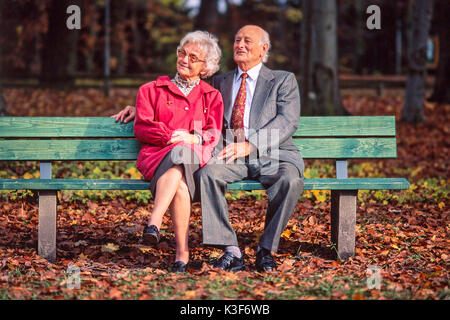 Senior citizen's couple sits together on a wooden bench at the wood - Stock Photo
