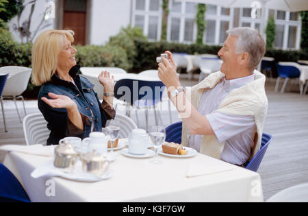 Man takes a photo of woman at the cafe - Stock Photo