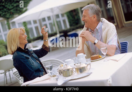 Woman takes a photo of man at the cafe - Stock Photo