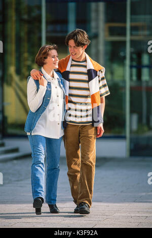 Young couple runs side by side, boy has placed arm around the girl - Stock Photo