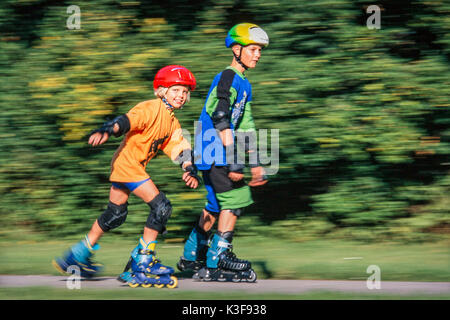 Boy and girl close the inline skating - Stock Photo