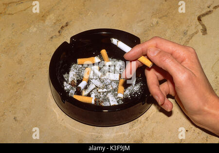 Smoker close burning cigarette in the hand and ashtray - Stock Photo