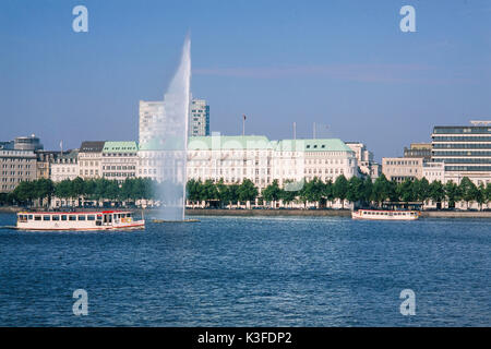 Water jet on the Inner Alster in front of the Fairmont hotel Four seasons, Hamburg - Stock Photo