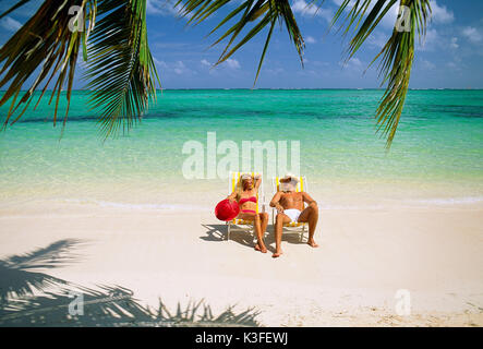 Young couple at the deck chair at the beach - Stock Photo