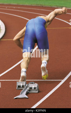Sprinter while starting from the starting block - Stock Photo