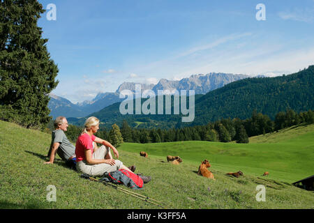 Couple on a meadow in front of mountain panorama Wetterstein Range - Stock Photo