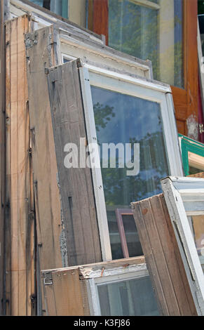 Heap of old wooden window frames with glass outdoors. Broken ...