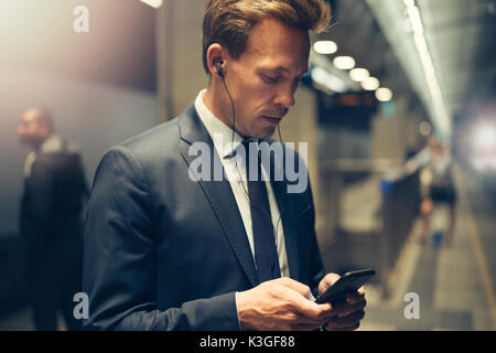 Young businessman wearing earphones and sending text messages on his cellphone while standing on a subway platform - Stock Photo