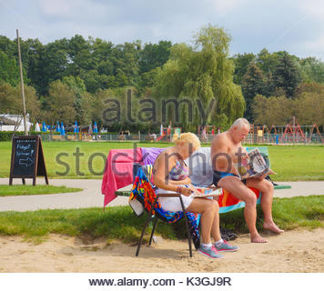 Man and woman in bathing clothes reading a magazine and newspaper while sitting on a wooden bench at a park on August - Stock Photo